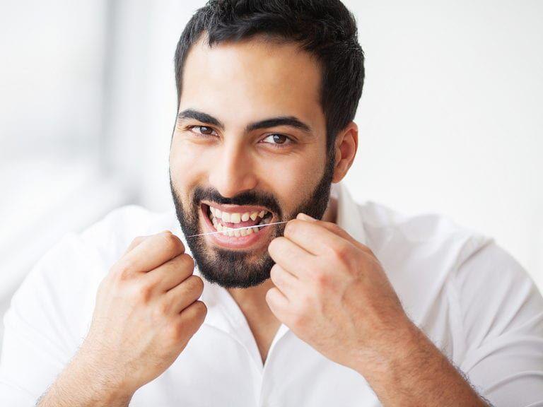 Man flossing gaps in teeth